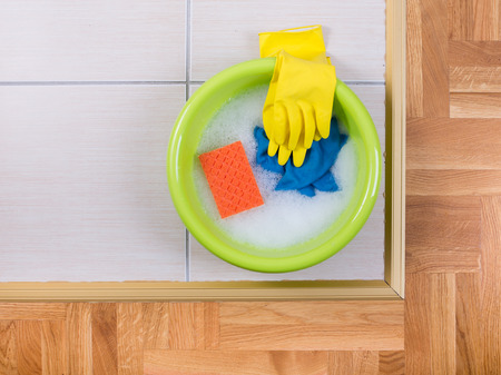 washbasins: Top view of plastic washbasin with foam and cleaning tools on tiled floor