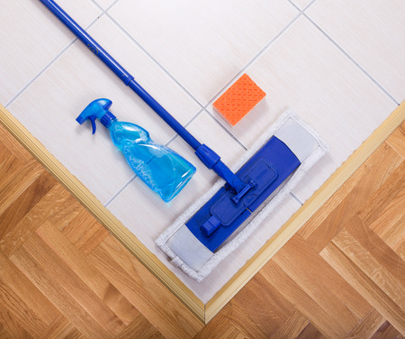 chemical bottle: Close up of mopping cleaning tools on tiled floor Stock Photo