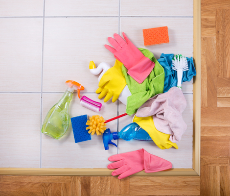wood house: Cleaning supplies on a pile on tiled floor. Group of colorful cleaning tools. Top view