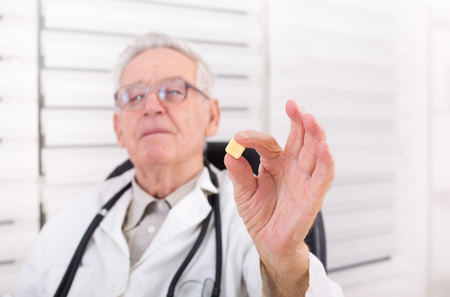 pharmacologist: Senior doctor holding and looking at square shaped pill in his office