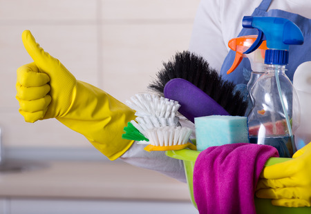 House keeper holding basin full of cleaning supplies and showing thumb up in front of clean kitchen Standard-Bild