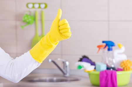 House keeper showing ok sign with thumb up in front of clean kitchen countertop with basin and cleaning supplies in it