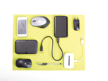 plug in: Top view of gadgets on green pad on white desk