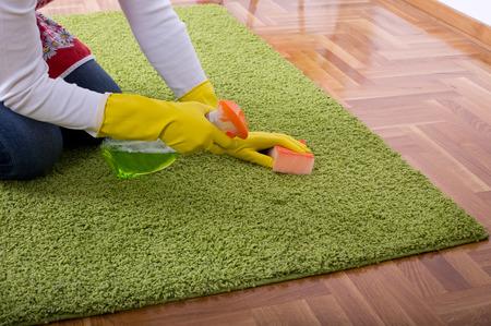 mujer limpiando: Cierre plano de las manos con guantes de protección de la alfombra de limpieza con una esponja y detergente líquido de la botella del aerosol