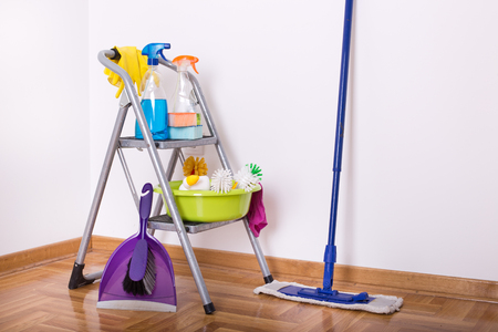 Cleaning supplies on ladder and mop and brush with dustpan on the parquet in the corner of room Stockfoto