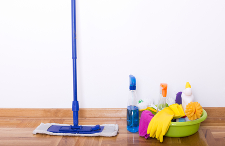 Mopping stick and washbasin full of cleaning supplies and equipment standing on parquet beside white wall