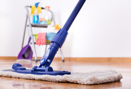 Close up of mop on the parquet and cleaning supplies on the ladder in background Archivio Fotografico
