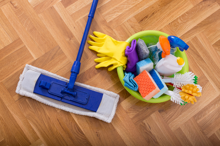 household equipment: Top view of mopping stick and washbasin full of cleaning supplies and equipment on the parquet Stock Photo