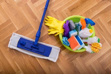 limpieza  del hogar: Vista superior de fregar palo y lavabo lleno de suministros y equipos de limpieza en el parqué