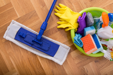 House cleaning concept. Top view of cleaning supplies in the wasbasin and mop on the parquet