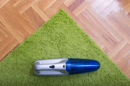 Top view of cordless handheld vacuum cleaner on green fluffy carpet on the parquet