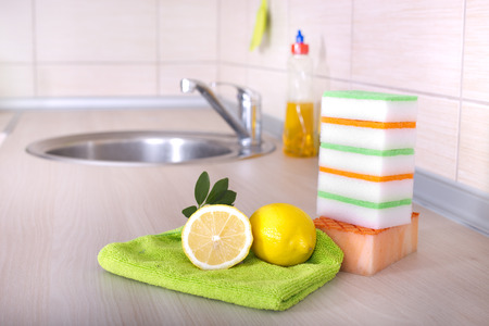 dishwashing: Dish washing concept. Close up of lemon and sponges for dishwashing on the kitchen countertop. Bottle and faucet in background