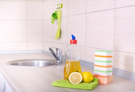 lavar platos: concepto de lavado de platos. Cierre de limón, detergente en botella y las esponjas para el lavaplatos en la encimera de la cocina