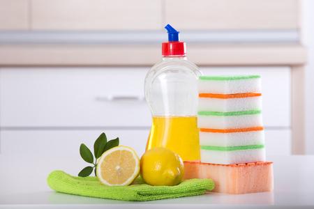 dishwashing: Dish washing concept. Close up of lemon and sponges for dishwashing on the kitchen countertop. Kitchen countertop and drawer in the background Stock Photo