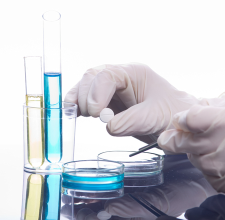 pharmaceutical: Close up of scientists hands holding tablet above petri dish. Medical research concept