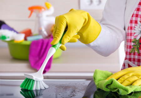 scrubbing: Close up of human hand with protective gloves cleaning induction hob with scrubbing brush and rag. Cleaning supplies in background Stock Photo
