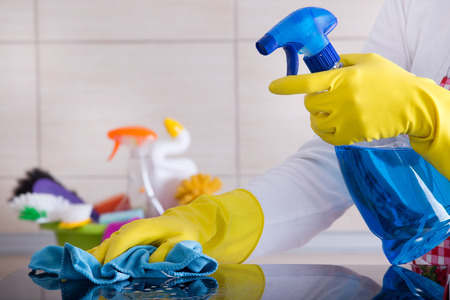 cleaning background: Close up of human hand with protective gloves cleaning induction hob with rag. Cleaning supplies in background