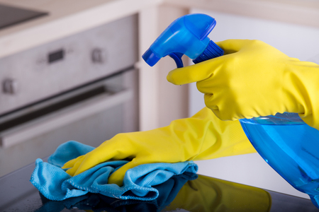 spray bottle: Close up of human hand with protective gloves cleaning induction hob with rag and holding spray bottle. Stove in background