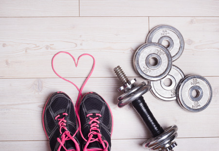 shoe laces: Sport lifestyle concept. Top view of dumbbells and sneakers on the bright wooden floor. Heart shape with shoe laces Stock Photo