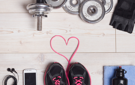 sneakers: Sport lifestyle concept. Top view of dumbbells, sneakers and sport accessories on the bright wooden floor. Heart shape with shoe laces