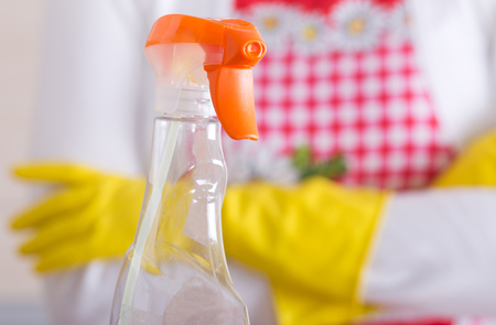 spray bottle: Close up of spray bottle for house cleaning. Woman with apron and rubber gloves standing in background with crossed arms