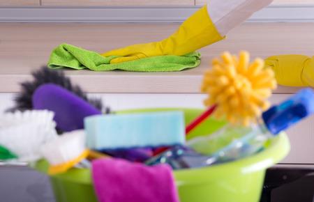 mujer limpiando: Guardián de la casa limpiando encimera de la cocina con un paño. Artículos de limpieza en lavabo borrosas en planta frontal