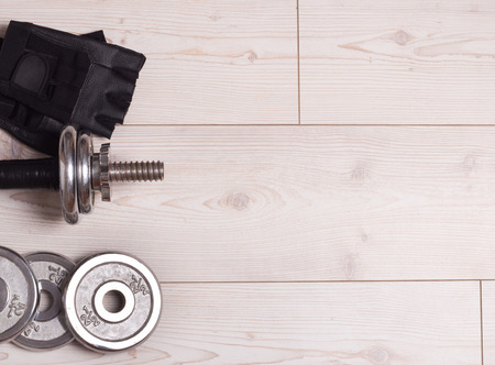 additional training: Top view of dumbbells, extra weights and gloves on the bright wooden floor