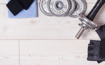 additional training: Top view of dumbbells and accessories on the bright wooden floor Stock Photo