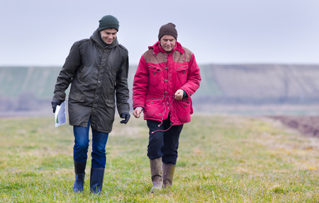 plowed field: Two farmers walking on plowed field in winter time