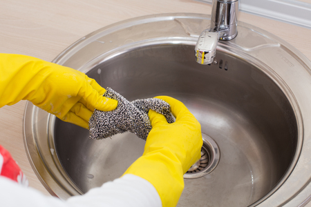 lavar platos: Cerca de las manos de humanos que exprimen la esponja después de lavar los platos en la cocina Foto de archivo