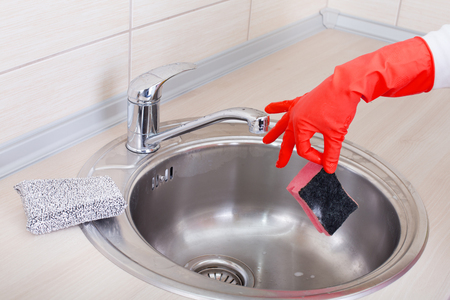 dish washing gloves: Close up of female hand holding sponge with two finger above kitchen sink, expressing disgust