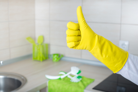 cleaning business: Conceptual image of home cleaning. Close up of human hand with yellow rubber glove showing ok sign with thumb up. Clean kitchen countertop and furniture in background Stock Photo