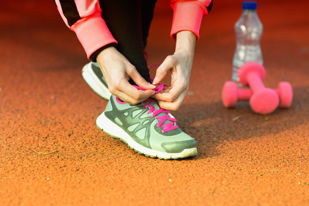 lacing sneakers: Close up of girls hands tying sport shoes at outdoor gym. Dumbbells and water bottle in background