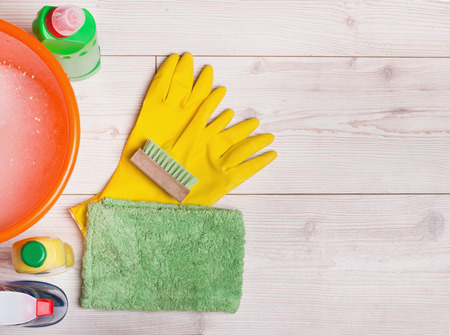 cleaning gloves: Top view of cleaning supplies and tools for house keeping on the bright laminate floor Stock Photo
