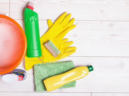 household equipment: Top view of cleaning supplies and tools for house keeping on the bright laminate floor Stock Photo