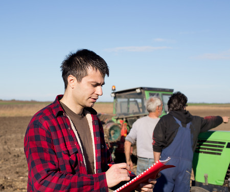 landowner: Young handsome farmer standing on farmland and writing notes. Workers and tractors in background Stock Photo