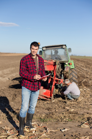 landowner: Young handsome farmer standing on farmland. Tractor and worker in background Stock Photo