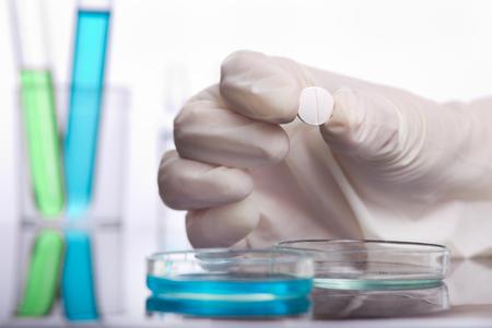 Gros plan des mains de scientifique tenant la tablette au-dessus de la boîte de Pétri. Concept de recherche médicale