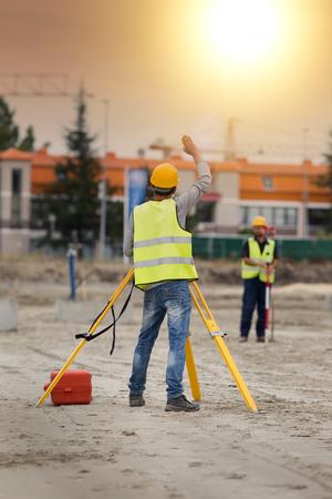 topógrafo: Ingenieros Surveyor trabaja con teodolito en el sitio de construcción de carreteras