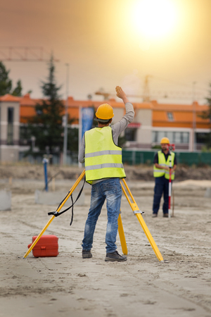 leveling instrument: Surveyor engineers working with theodolite on road construction site