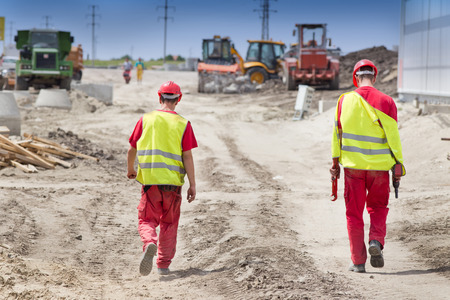 Achter mening van twee bouwvakkers lopen op bouwterrein met apparatuur. Bouwmachines in de achtergrond