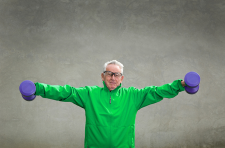 sports clothing: Senior man in his seventies training and lifting dumbbells