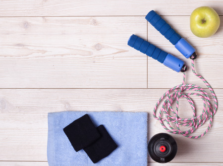 skipping rope: Top view of skipping rope, apple and other sport accessories on bright wooden floor. Sport and exercise concept