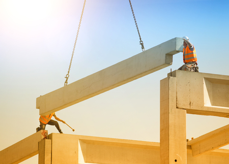 rigger: Construction workers standing on concrete beam on height and placing truss lifted by crane Stock Photo