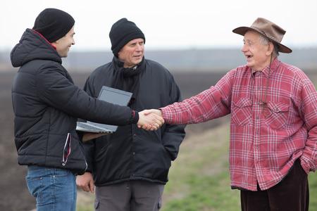 campesino: negocios que sacuden las manos jóvenes con viejo campesino en tierras de cultivo