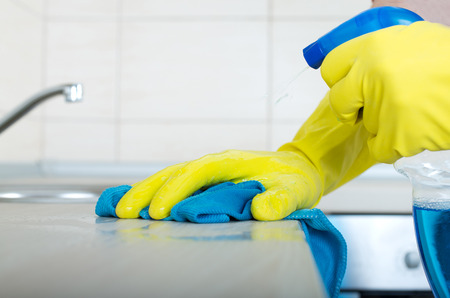 spray bottle: Close up of human hand in protective gloves holding mop and spray bottle and wiping kitchen countertop