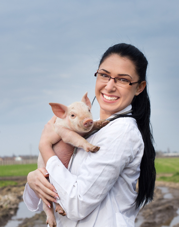 Happy young veterinarian girl holding cute piglet in her arms on the farm