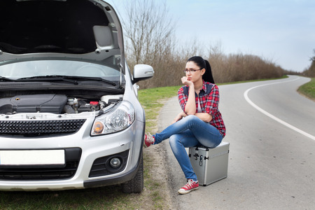 stopped: Young woman sitting on the suitcase beside stopped car with opened hood by the road Stock Photo