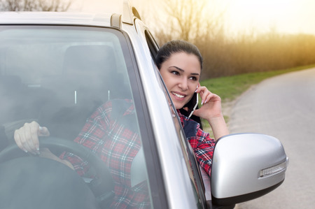 telephoning: Young pretty woman stopped car by the road and talking on the cell phone
