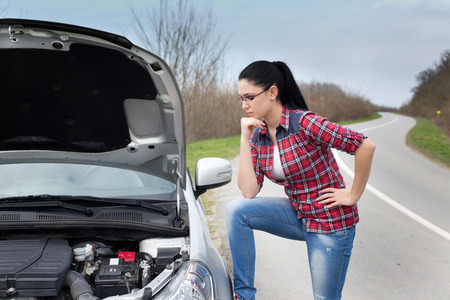 roadside stand: Young woman standing beside stopped car with opened hood and looking into engine beside road